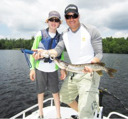 Fishing in the Adirondacks with a father and son catching a Northern Pike,
